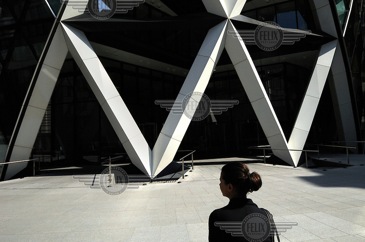 Business woman by the Swiss Re Building, colloquially known as 'the Gerkin', and officially as 30 St Mary Axe, London. The building was designed by British architect Sir Norman Foster.