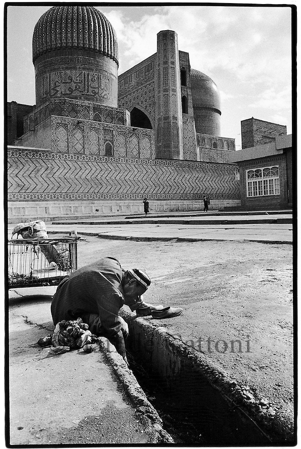 Uzbekistan - Samarkand - An old man washing vegetables inside the irrigation canal near Bibi Khanum mosque, used in Soviet times as a cotton warehouse.