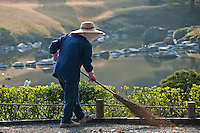 A traditionally-dressed gardener sweeping a gravel path at the Suizen-ji water garden