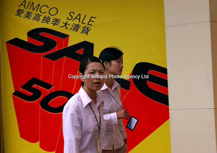 "A couple of shop assistants pass a ""For Sale"" sign in Kunming, China..14 Jul 2005"