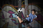 A young boy plays street soccer against a graffiti covered wall - with dramatic lighting and subdued colors - EXCLUSIVELY AVAILABLE on ALAMY http://www.alamy.com/stock-photo-a-young-boy-plays-street-soccer-against-a-graffiti-covered-wall-with-67184272.html