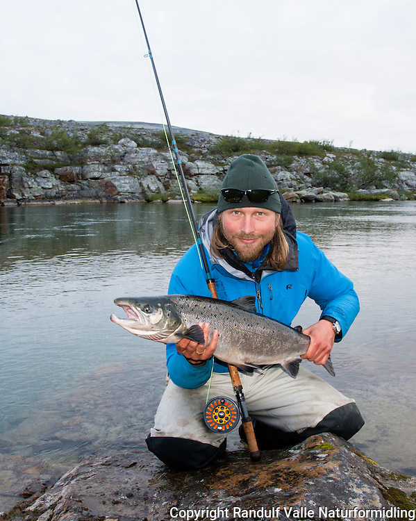 Mann med mellomlaks på sone 3 i Børselva. ---- Man and salmon in Børselva, Finnmark.