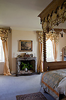 The windows of a four-poster bedroom are dressed with curtain pelmets to match the bed hangings