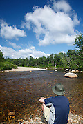 Man sitting on the side of the Ammonoosuc River in Carroll, New Hampshire USA.