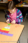 Public school grade 4 girl working on mathematics fractions exercise using paper cut in different sizes to represent fractions hands on learning vertical