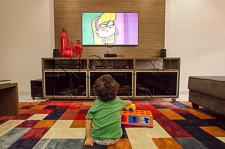 Criança assistindo televisão com brinquedo, São Paulo - SP, 10/2014.                            - Uso de imagem autorizado