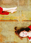 A young woman lying on the ground wearing a red dress