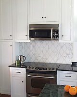This custom kitchen features a Djinn mosaic backsplash shown in polihed Calacatta Tia from the Silk Road Collection by Sara Baldwin for New Ravenna.<br />