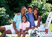 Young black family sitting together in backyard.