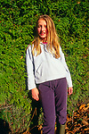 A08BX1 Young girl with blonde hair against green hedge
