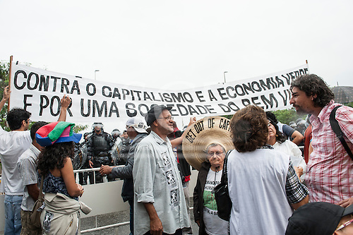 Anti-capitalist protestors unfurl a banner in front of shock troops at a demonstration by indigenous people, the Landless People's Movement (MST) and other civil society groups in front of the Riocentro United Nations conference. The demonstrators are kept out of earshot and invisible to the UN conference. The United Nations Conference on Sustainable Development (Rio+20), Rio de Janeiro, Brazil, 20th June 2012. Photo © Sue Cunningham.