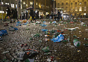 Locals make their way through the broken glass and empty bottles as the clear up gets underway at Dam Square, Amsterdam after the Celtic fans party ahead of the game against Ajax.