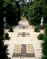 A formal patio in brick and stone built for Sir Roy Strong by his wife and planted with Buxus, conifers and Tropaeolum