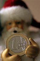 Santa Claus doll holding out a euro coin.