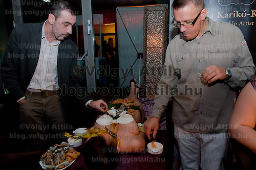Male guests eat sushi served on the body of naked woman following japanese traditions in a club in downtown Budapest, Hungary on September 23, 2011. ATTILA VOLGYI