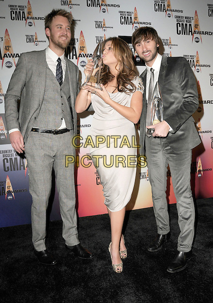 LADY ANTEBELLUM - Charles Kelley, Hillary Scott, and Dave Haywood.Attending the 43rd Annual CMA Awards held at the Sommet Center, Nashville, Tennessee, USA, 11th November 2008..pressroom press room country music .full length grey gray beige suit dress trophy kissing award funny band group winner winners gold peep toe shoes trophies .CAP/ADM/GS.©George Shepherd/AdMedia/Capital Pictures.