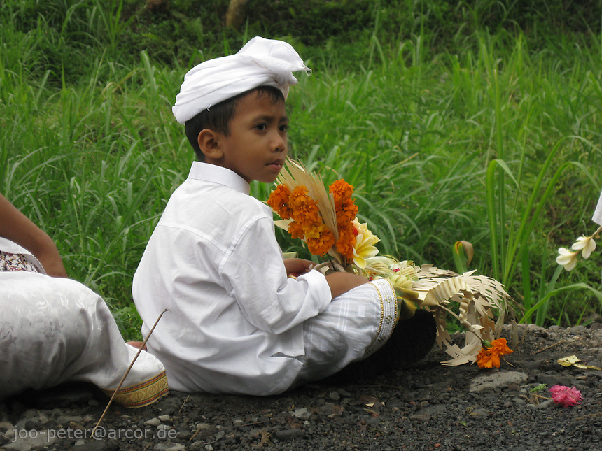 child is watching ceremonies at the river after cremation took place in the village, mountain village Muncan, Bali, archipelago Indonesia