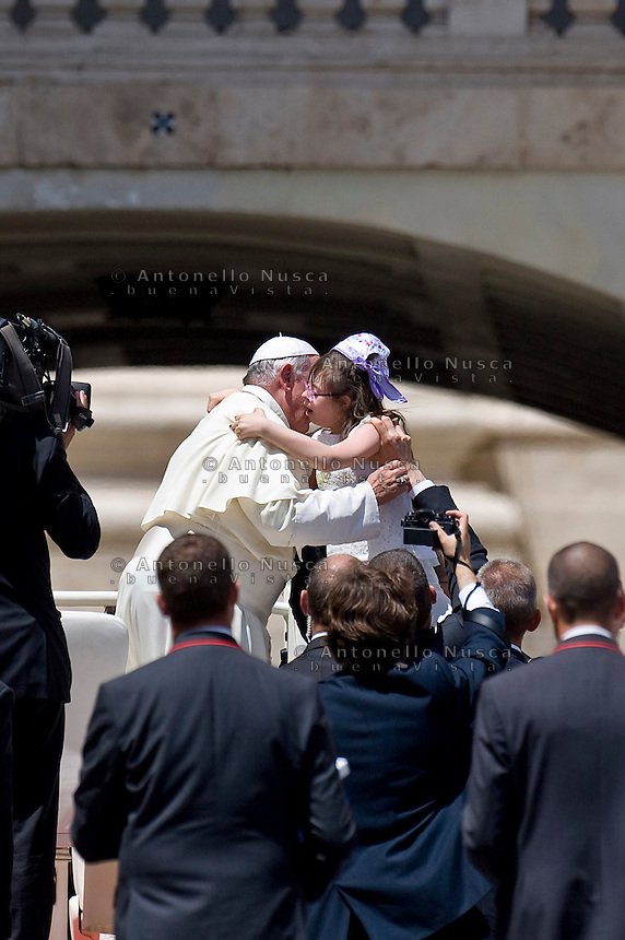 Papa Francesco abbraccia una bambina down al termine della udienza in Piazza San Pietro. Pope Francis embraces a baby down as he leaves St. Peter's Square at the end of his weekly audience.