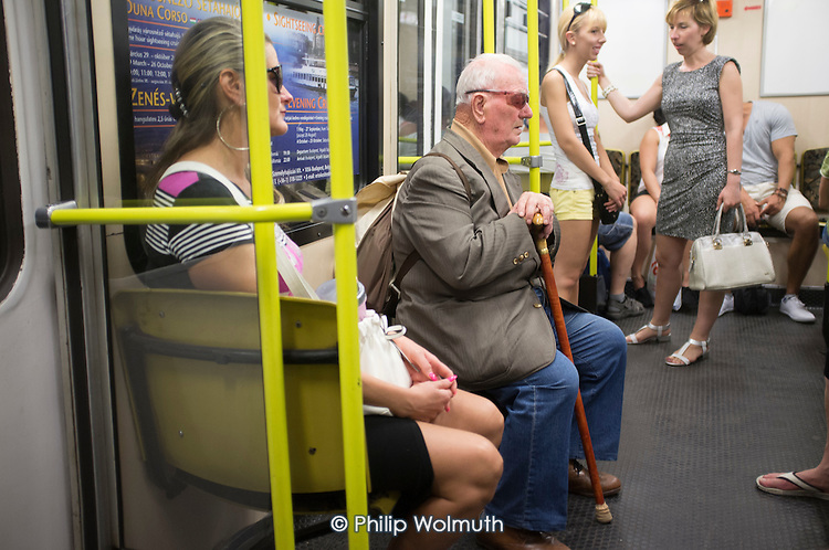Elderly man with a walking stick and glassees on a metro train, Budapest.