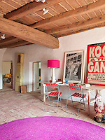 Bursts of bright purple, pink and red in the rug, lamp and chairs of the entrance hall give it a contemporary and vibrant feel