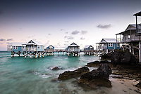 Small wooden houses placed on stilts on top of the water in the Seven Beaches resort in Bermuda, Atlantic Ocean
