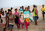 COX'S BAZAR, BANGLADESH - APRIL 24:  12 year old Shuma, 10 year old Jahanara, and 12 year old Shumi are seen with other surfers after posing for a group photo at the Cox's Bazar annual surf competition April 24, 2014 in Cox's Bazar, Bangladesh. A group of 10-12 year old female beach vendors, most of whom have dropped out of school to help support their families, have been learning to surf for the past three months in preparation for the annual Cox's Bazar surf competition. 24 year old surfer, lifeguard and beach worker Rashed Alam, has been teaching and mentoring the girls for 3 months. Like the girls, Alam dropped out of school and started working on the beach to help support his family at a young age. He started surfing when he was 16. He says that his way of giving back is by ensuring that girls get a good future through surfing. (Photo by Allison Joyce/Getty Images)