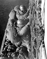 Troops are climbing down cargo net to waiting LCVP's as they land.  January 9, 1953. (Army)<br /> NARA FILE #:  111-SC-FEC-53-402<br /> WAR &amp; CONFLICT BOOK #:  1417
