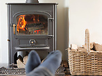 Roaring domestic household wood burning ClearView stove fire log basket with feet up in foreground,