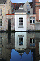 BRUGES, BELGIUM - FEBRUARY 06 : A detail of a small white wall with window covered by a roof in the shape of a bell, in the middle of coloured walls of brick overlooking a canal, on February 06, 2009 in Bruges, West Flanders, Belgium. The sky finds its place in the reflection of the water and embellishes the sparkling white of the small and probably official building in medieval times. (Photo by Manuel Cohen)