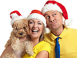 Portrait of a happy young man and a woman with a Cockapoo dog in her hands wearing red Christmas hats.