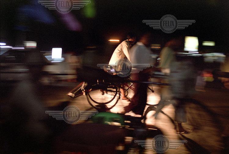 People cycle and walk along an urban street in Rangoon (Yangon) at night time. ..