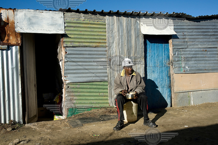 Albert Monaheng, a miner working at the Kroondal Mine, sits outside his shack.