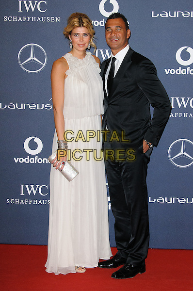 Estelle Cruyff and Ruud Gullit.Arrivals at the Laureus 2012 World Sports Awards held at the Queen Elizabeth II Centre, London, England..February 6th, 2012.full length black dress suit white dress.CAP/CJ.©Chris Joseph/Capital Pictures.