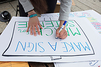 """A Harvard student makes a sign reading """"Make a sign for the March for Science"""" to entice others to make protest signs before the March for Science demonstration in Harvard University's Science Center Plaza in Cambridge, Massachusetts, on Sat., April 22, 2017."""