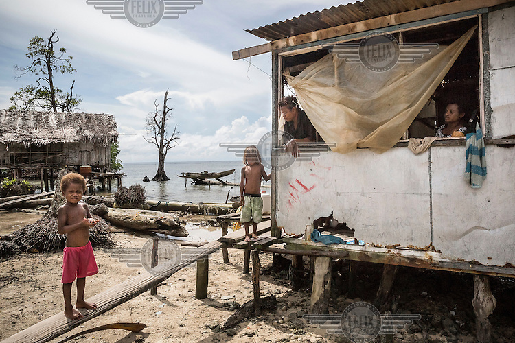 Josephine Kiou (in the middle), a mother of four children, sits at the window of her home with her sister watching their children playing outside. Her house was destroyed by a 'king tide' in 2012 but all the island's residents helped her to rebuild it.