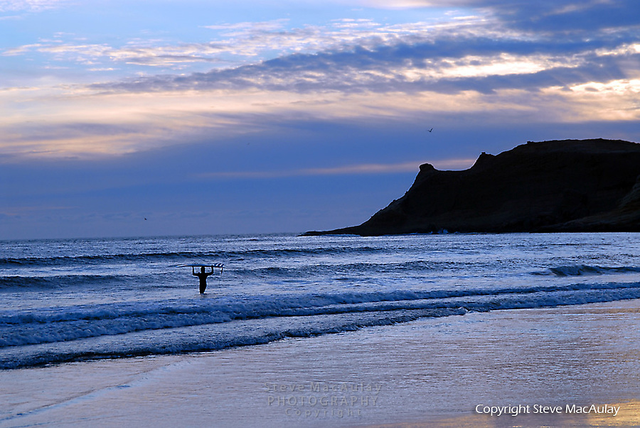 Surfer at Pacific Beach, Oregon at sunset