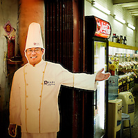 A cut-out cardboard chef welcomes people to a restaurant and food store.