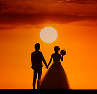 A couple holding hands at their sunset wedding in Hawai'i.