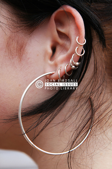 Side view of a young woman with multiple ear piercing,