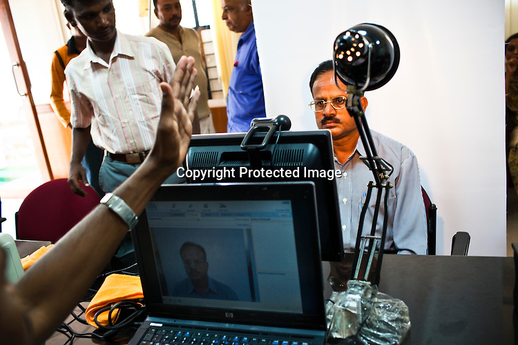 An employee instructs Dr. B.Malikarjuna to move while he sits in front of camera for the enrollment process in Karnataka, India. Photograph: Sanjit Das/Panos