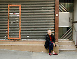 Hong Kong urban scene - old Chinese woman sits on step