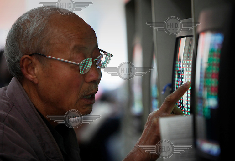 An elderly man checks the current prices of stocks displayed on a monitor in a securities exchange house.