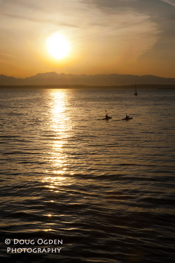 Kayakers on Elliot Bay during sunset, Olympic Mountains in background Seattle, Vertical