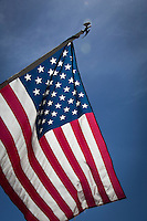 The United States Flag waving against a blue sky with high thin clouds.