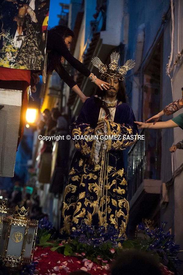 The faithful from the balconies of their houses trying to touch the image of Jesus Christ to the passage of the procession of the Holy Cross