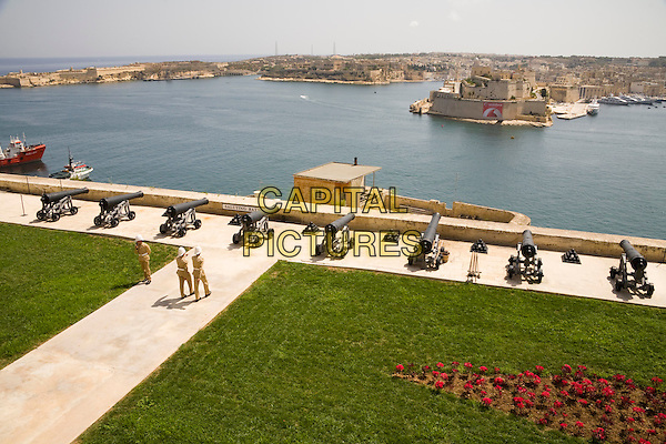 Soldiers and cannons at the Saluting Battery, and Grand Harbour, from Upper Barracca Gardens, Valletta, Malta