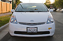 A front view of a white Toyota Prius with a 'SAV3 GAS' (Save Gas) license plate and a clean air vehicle sticker. Mountain View, California, USA