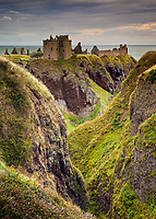 "Dunnottar Castle (Scottish Gaelic :Dùn Fhoithear, ""fort on the shelving slope"") is surrounded by steep cliffs looking over the North Sea.  This medieval fortress is located about 2 miles south of Stonehaven, Scotland and is the subject of a long and often brutal history."