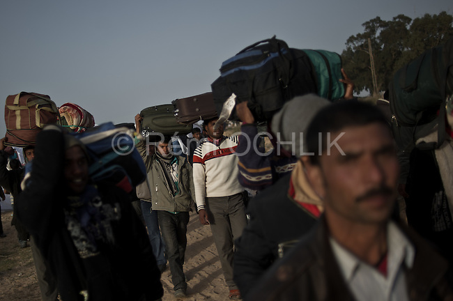 © Remi OCHLIK/IP3 -   RAS JEDIR, Tunisia 04 - Men from Bangladesh, who used to work in Libya but recently fled the unrest, wash at a refugee camp after crossing the Tunisia-Libyan border, in Ras Ajdir, Tunisia, Friday, March 4, 2011. Bangladeshis were angry at their country's government for not doing more to get the refugees home. Most of the Bangladeshis appear to have arrived in Tunisia penniless because their Libyan employers did not pay them or because they were robbed on the way.