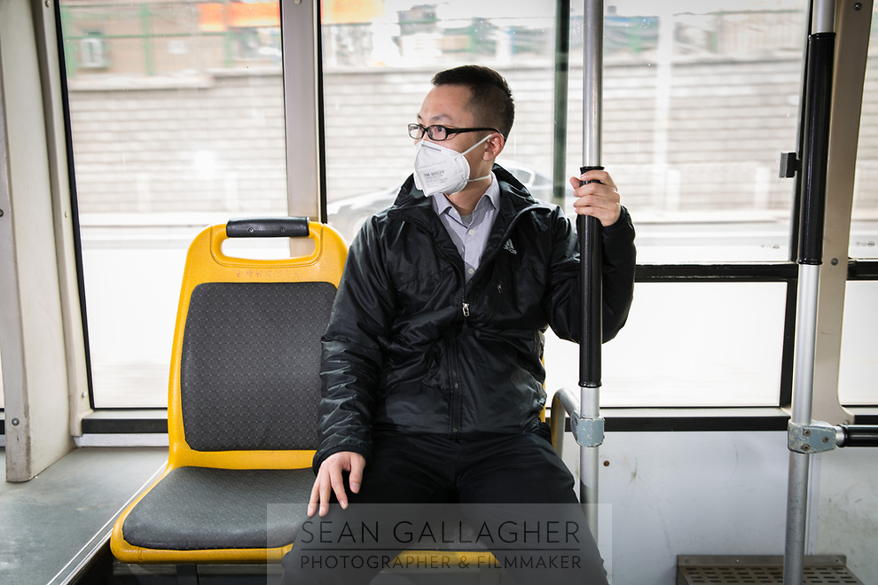 """Tony (Chinese name withheld), a 32-year old office worker rides a bus home during his lunch break in central Beijing. """"From 2013, I started using the mask. At that time the media reported the air was very serious. It was the first time it was said to be smog"""", he explains. He uses online apps to monitor the air pollution levels each day. """"If the index is over 200, I use it. Over 400? You must use it! I've asked my family and friends to wear the mask, especially when it's over 200"""". PM2.5 reading - 212 - Very Unhealthy"""